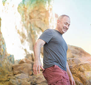 Man wearing grey shirt and red pants hiking