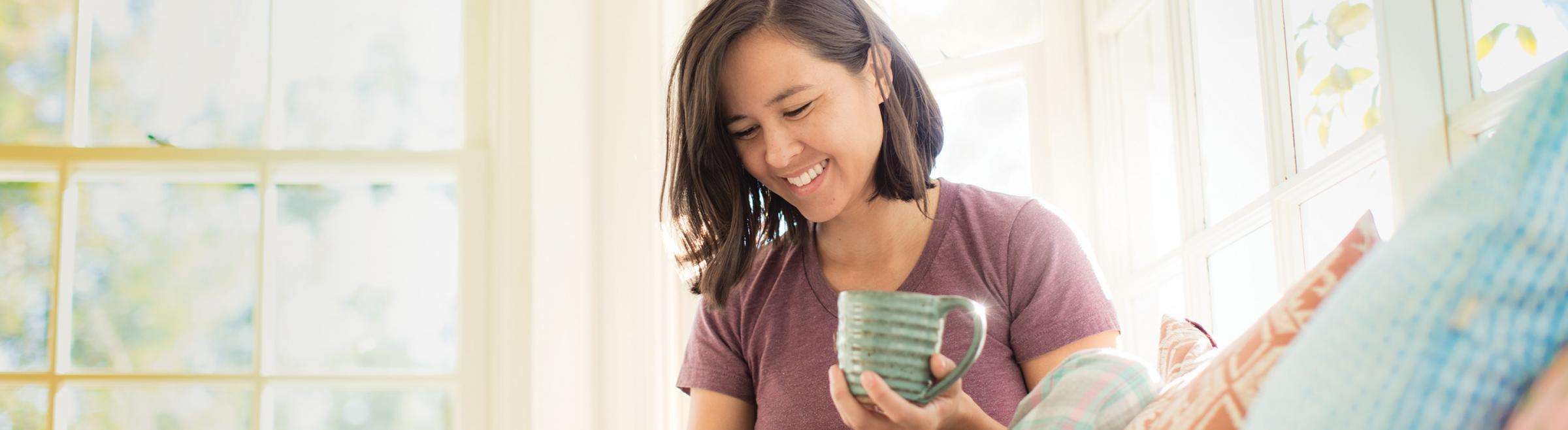 Woman drinking coffee and smiling in bright living room