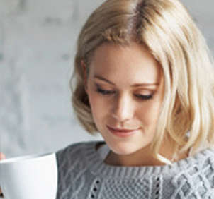 Blonde woman holding white coffee mug