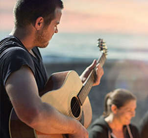 Man playing acoustic guitar for friends on beach