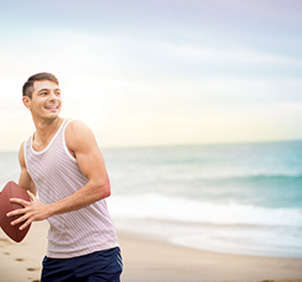Man in tank top throwing football on beach