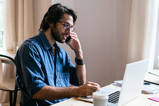 Bearded man with glasses working on laptop