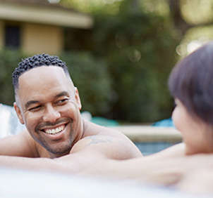 Man smiling at woman in pool
