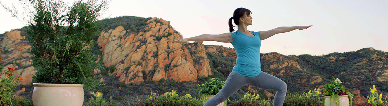 Woman doing Virabhadrasana (warrior pose) during yoga