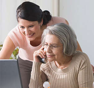 Woman helping older woman on her laptop