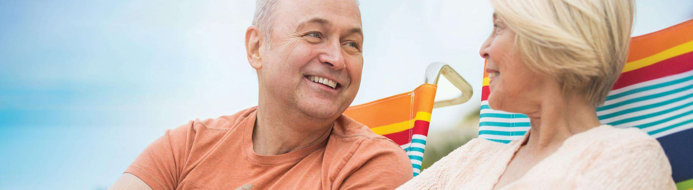Older couple sitting on beach chairs